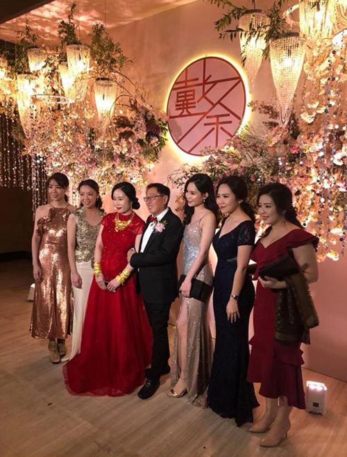 Cô dâu (váy đỏ) đứng bên chú rể chụp ảnh cùng khách mời.