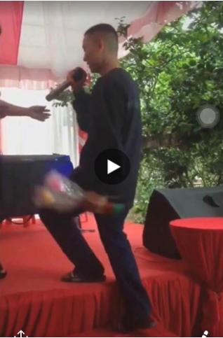 Hình ảnh Hoài Lâm cạo đầu trọc, đi dép lê, ăn mặc luộm thuộm trong một sự kiện.