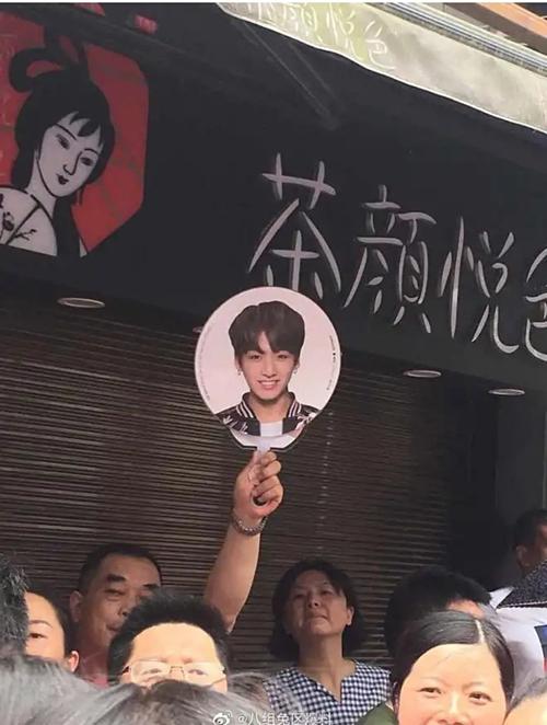 Sợ con gái lạc giữa đám đông, một ông bố đã giơ cao chiếc quạt in hình Jung Kook - thần tượng của con gái.
