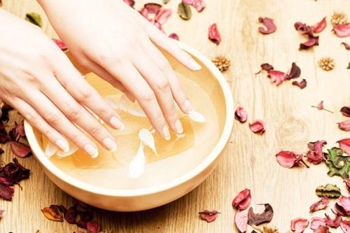 Ngâm tay trong nước muối để giảm tình trạng thô cứng của vết chai