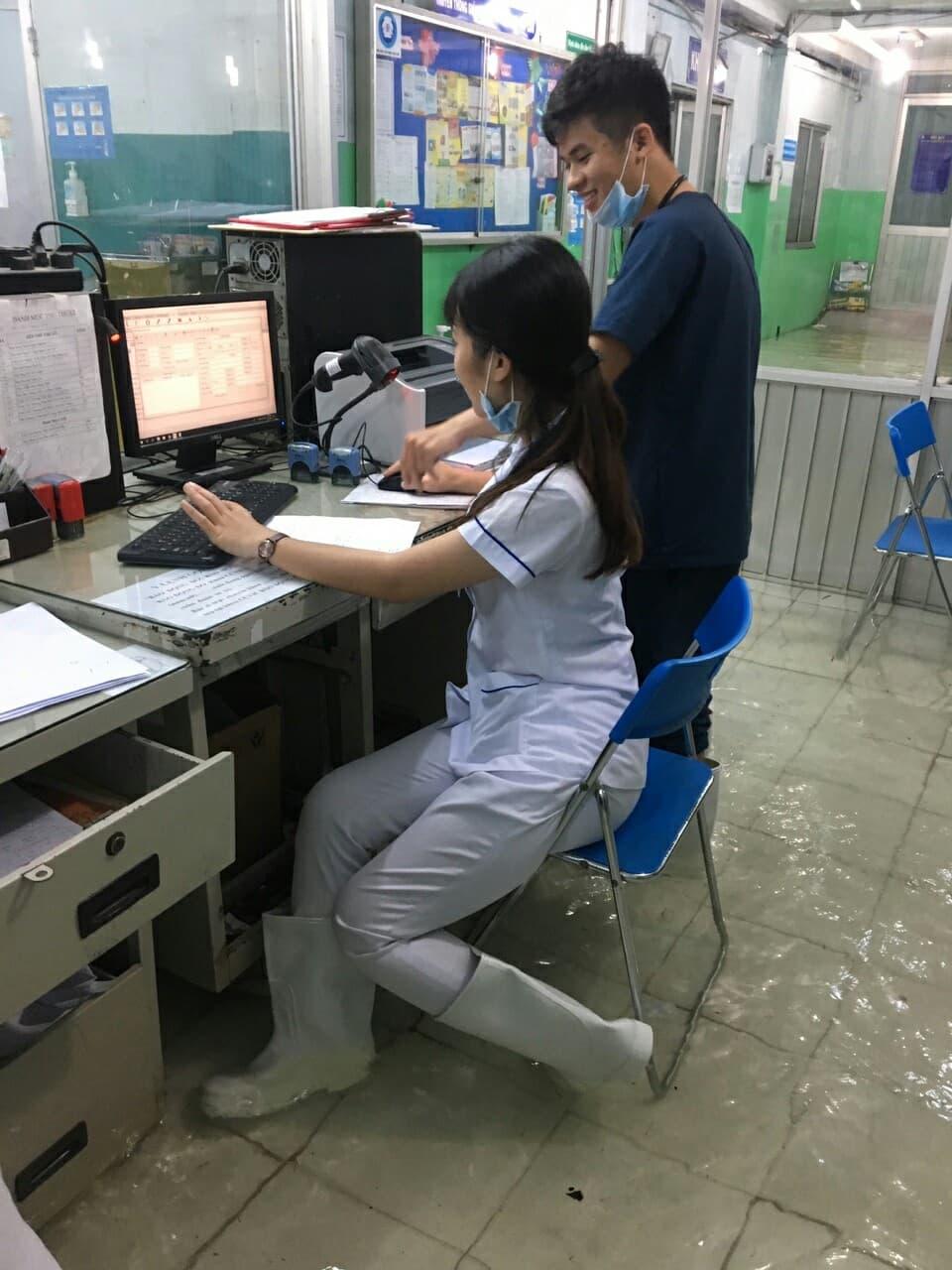 Bệnh viện ở Sài Gòn ngập sâu nửa mét, bác sĩ mang ủng đi khám cho bệnh nhân - Ảnh 1