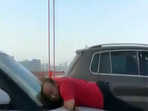 Người đàn ông ôm cây chổi bám chặt đầu xe ô tô