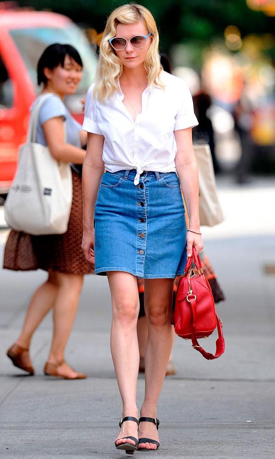 Kristen Dunst lựa chọn phong cách retro khi phối chân váy denim cài cúc với áo sơ mi trắng cộc tay, đuôi áo buộc ngang cạp váy.