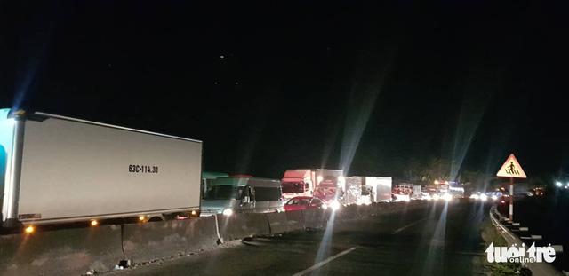 Đến hơn 20 h tối 10-2, ở tuyến tránh TP Vĩnh Long, xe cộ nối đuôi dài toàn tuyến không chờ lực lượng chức năng xả chốt lên cầu - Ảnh: CHÍ QUỐC