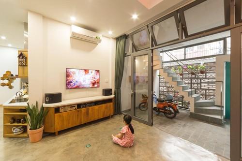 Tầng 1 là khu vực sinh hoạt chung của gia đình 3 người, với phòng khách rộng rãi. Không gian được kéo dài ra luôn khu bếp. Nền nhà là chất liệu bê tông xoa phẳng và điểm bằng các viên gạch gốm xanh ngọc.