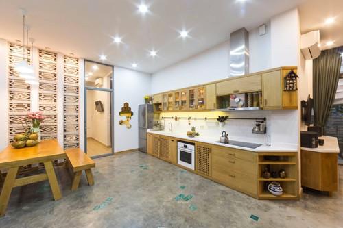 Khu vực bếp hiện đại với điểm nhấn là bộ bàn ăn, kệ đều bằng gỗ. Một phòng ngủ được đặt ngay bên cạnh, ngăn cách mùi bởi cửa kính.