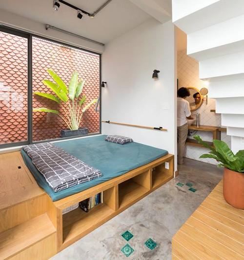 Một chiếc giường ngủ trên sàn gỗ được bố trí luôn ở đây. Hộc bên dưới được tận dụng để đựng sách, các tài liệu tham khảo...
