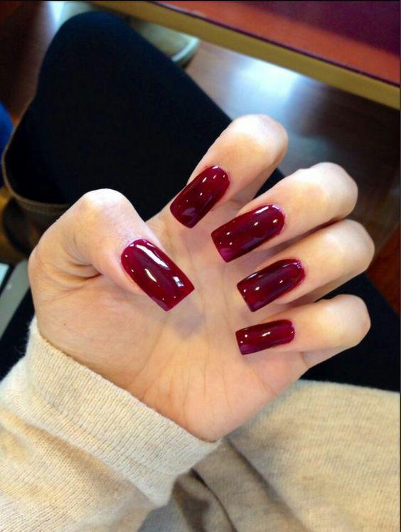Sơn móng tay màu đỏ bầm làm tôn lên đôi bàn tay trắng mịn