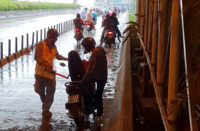 Phát áo mưa miễn phí tranh ùn ứ trong hầm ở TPHCM - Ảnh 1