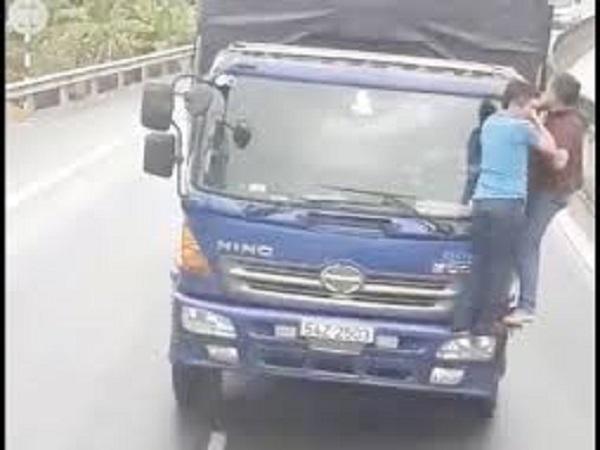 Hai người đàn ông 'diễn xiếc' trên đầu xe tải - Ảnh 1