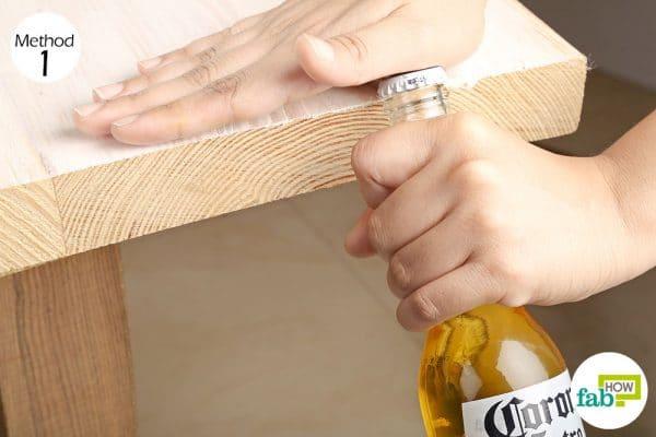 Tận dụng mặt bàn hay bất kỳ bề mặt cứng nào để mở bia chai nhanh chóng