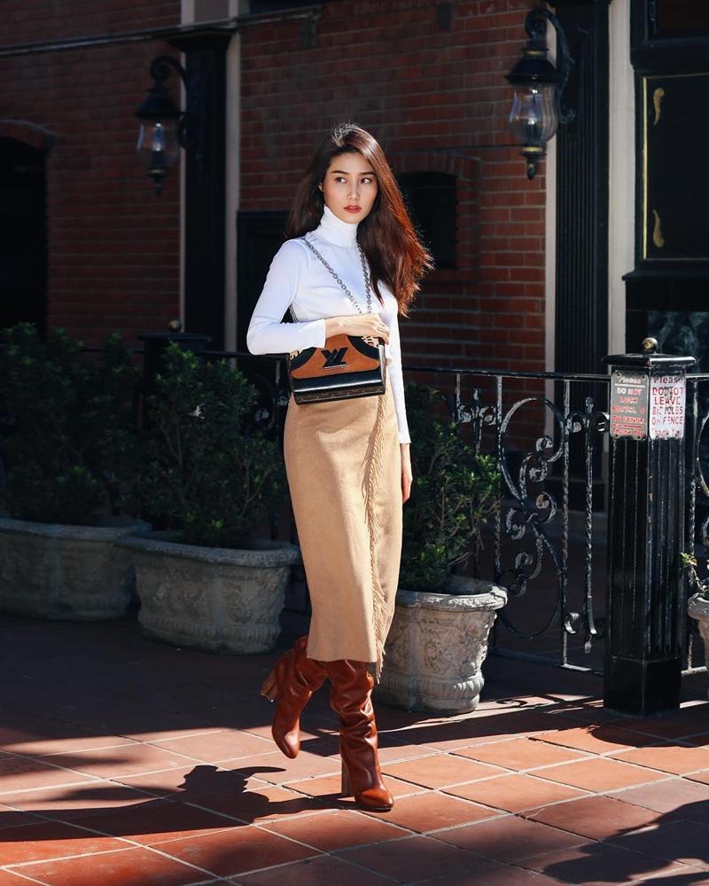 """Áo len cổ lọ và chân váy midi dáng bút chì, thêm một đôi boots màu nâu đất là Diễm My đã có được bộ cánh thể hiện rõ nét phong cách retro. Chiếc túi Twist của Louis Vuitton chính là điểm nhấn giúp set đồ trở nên sang trọng, """"đắt giá"""" hơn hẳn."""
