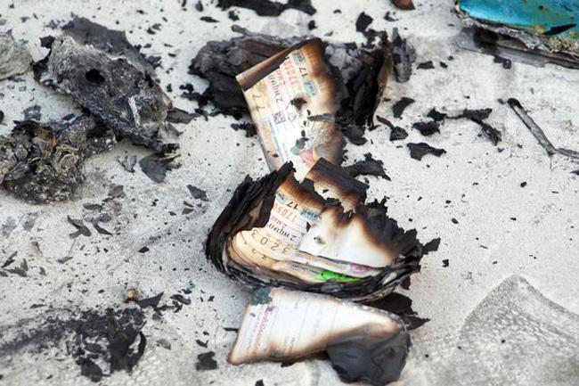 Những tấm vé số trượt giải cháy dở được tìm thấy trong túi của ông Peerapong Jirakunarat