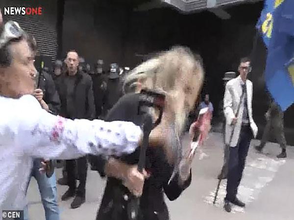 Trong video, một người phụ nữ xong tới tát vào mặt nữ phóng viên trẻ