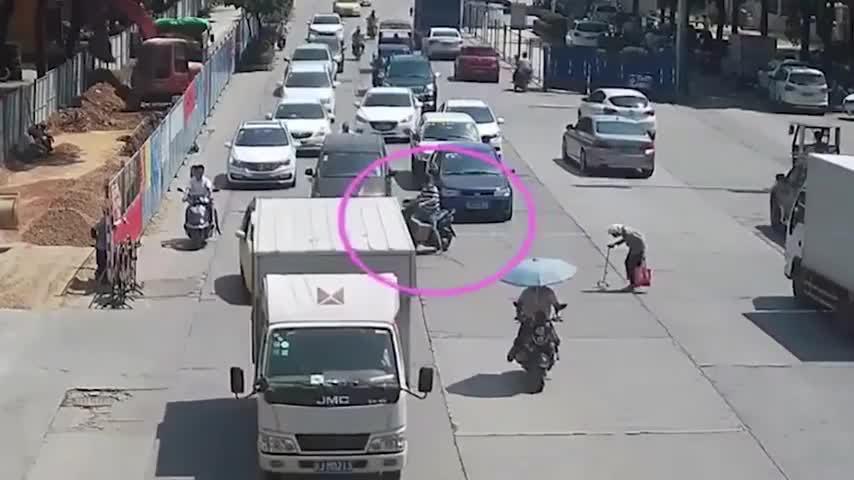 Người đàn ông lái xe máy chặn những phương tiện khác giúp cụ bà sang đường