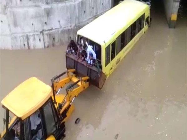 35 trẻ mắc kẹt trên xe buýt bị ngập nước, người dân mang máy xúc giải cứu - Ảnh 1