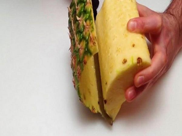 Bổ quả dứa làm tư, cắt bỏ lõi. Lia dao giữa vỏ và thịt quả để loại bỏ vỏ và mắt dứa, sau đó cắt thành lát mỏng.