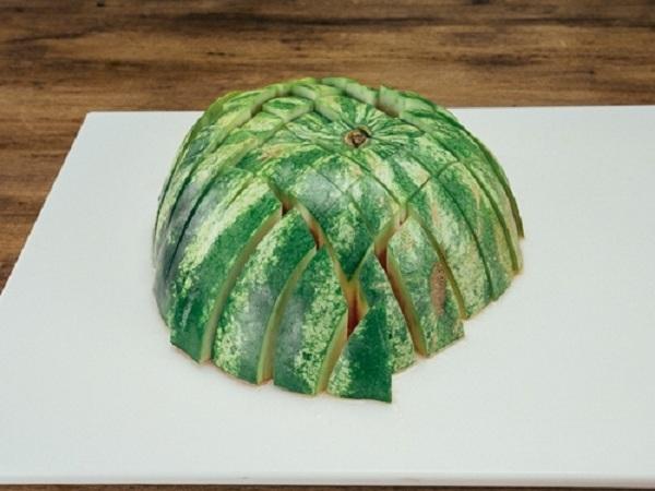 Bổ đôi quả dưa, đặt úp xuống thớt. Cắt thành hình lưới để được những miếng dưa nhỏ vừa ăn.