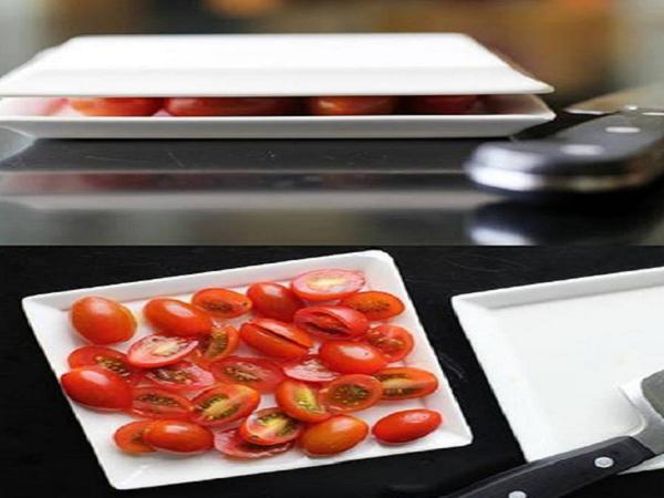 Đặt những quả cà chua giữa 2 chiếc đĩa, ấn xuống để giữ cà chua cố định rồi đưa dao qua khe hở giữa 2 chiếc đĩa để cắt đôi toàn bộ số cà chua.