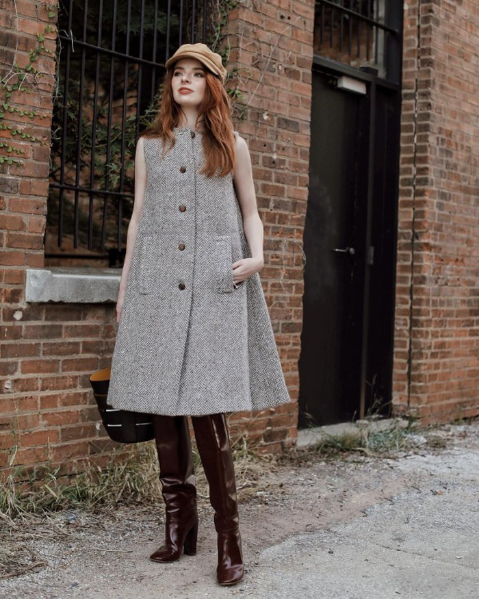 Jane Aldridge lựa chọn trưng diện một mẫu đầm liền sát nách chất liệu nỉ khá ấm áp. Để hoàn thiện bộ trang phục, cô sử dụng phụ kiện là mũ baker boy và boots đùi chất liệu da bóng.