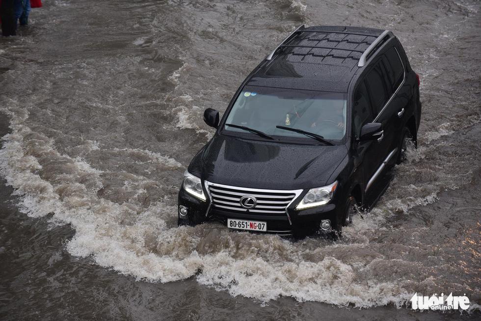 Người dân TP.HCM vật lộn trong mưa đầu mùa gây ngập nửa mét - Ảnh 1