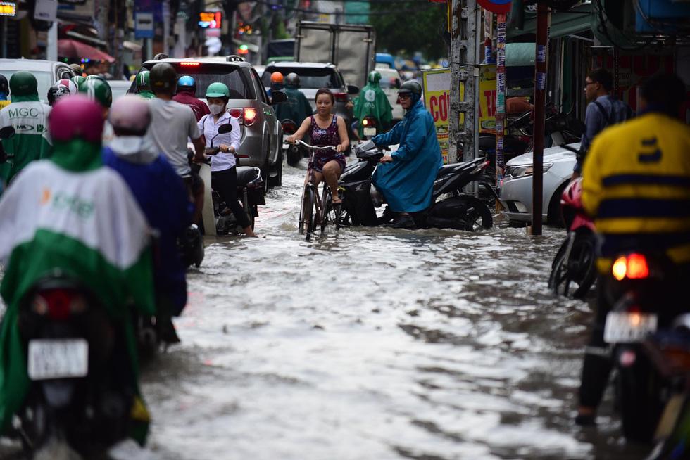 Người dân TP.HCM vật lộn trong mưa đầu mùa gây ngập nửa mét - Ảnh 10