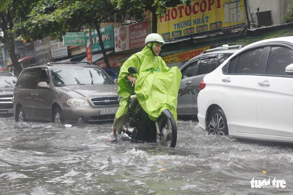 Người dân TP.HCM vật lộn trong mưa đầu mùa gây ngập nửa mét - Ảnh 7
