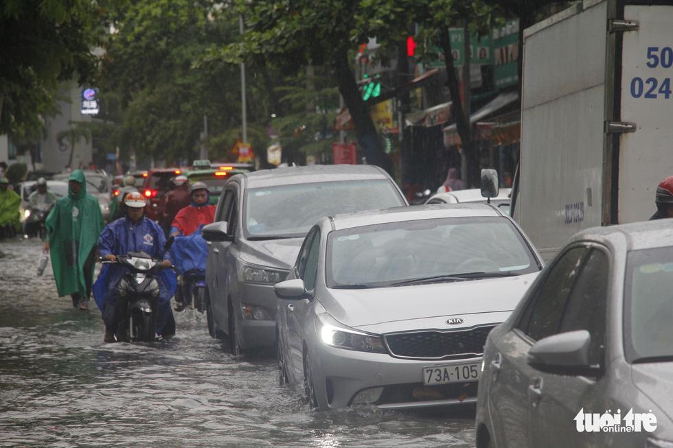 Người dân TP.HCM vật lộn trong mưa đầu mùa gây ngập nửa mét - Ảnh 8