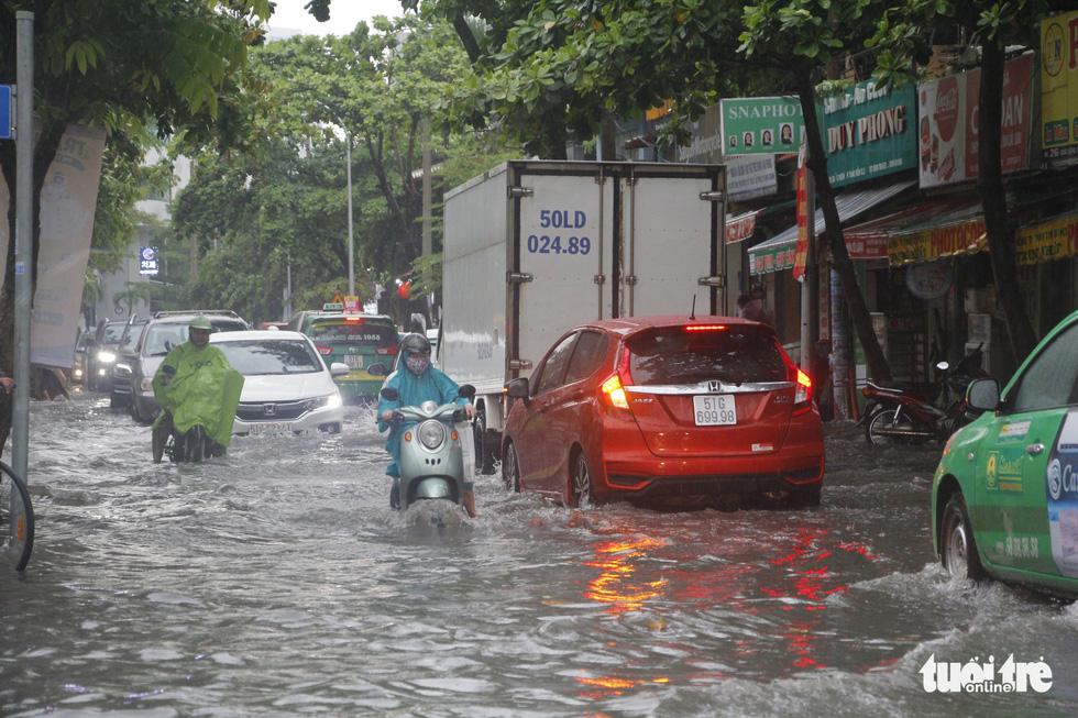 Người dân TP.HCM vật lộn trong mưa đầu mùa gây ngập nửa mét - Ảnh 9
