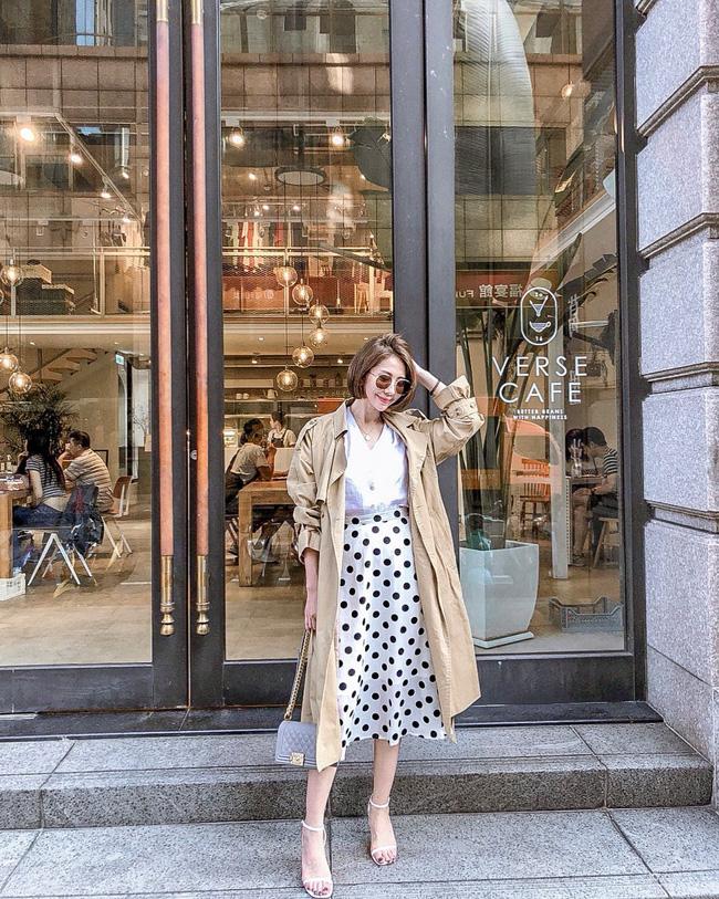 Các nàng hoàn taoàn có thể tận dụng chiếc áo blouse cùng chân váy chấm bi của mùa hè để cùng với trench coat tạo nên set đồ nữ tính và trang nhã như quý cô này; diện đến sở làm quả là không thể hoàn hảo hơn.a