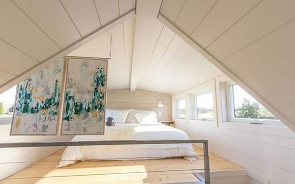 Giường ngủ trên gác mái ngập ánh sáng mặt trời.