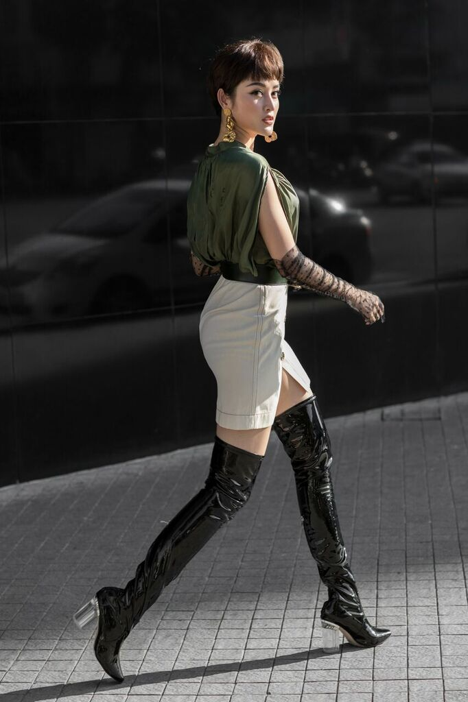 Với mái tóc ngắn cá tính, Huyền My nổi bật trên phố với bộ váy da bóng dáng chữ A, phối cùng áo sơ-mi trắng tay phồng và boots da quá đầu gối.