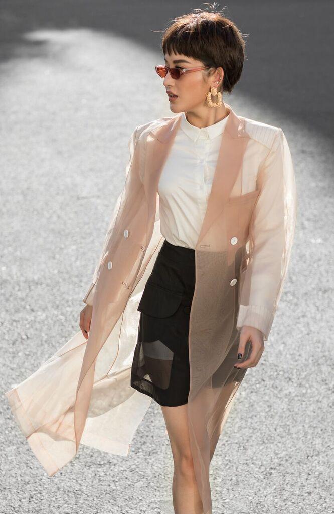 Phong cách áo choàng trong suốt cũng được Huyền My lăng-xê trong bộ ảnh lần này khi kết hợp cùng set đồ cơ bản là chân váy xuyên thấu màu đen và áo sơ-mi trắng.