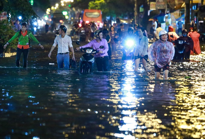 Mưa lớn, 'phố biến thành sông', người dân Sài Gòn bì bõm dắt xe 'bơi' về nhà - Ảnh 1