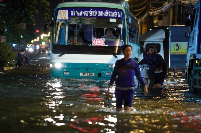 Mưa lớn, 'phố biến thành sông', người dân Sài Gòn bì bõm dắt xe 'bơi' về nhà - Ảnh 4