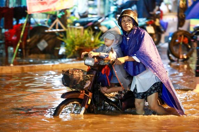 Mưa lớn, 'phố biến thành sông', người dân Sài Gòn bì bõm dắt xe 'bơi' về nhà - Ảnh 5