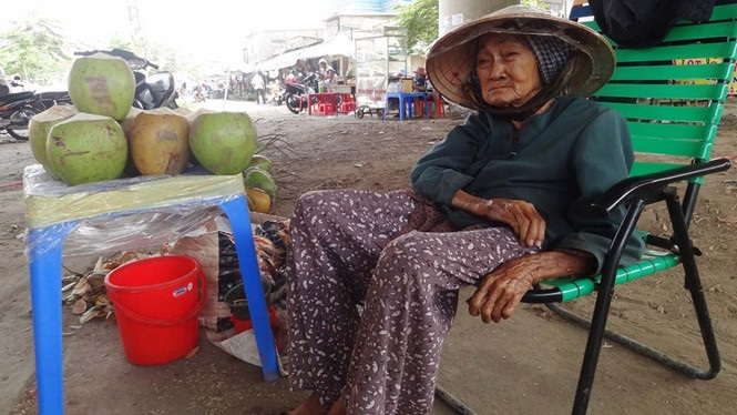 Xót xa cụ bà 89 tuổi bám gầm cầu bán dừa kiếm sống - Ảnh 1