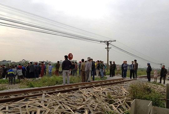 Tàu hỏa tông 2 người đi xe máy văng xuống ruộng tử vong - Ảnh 1