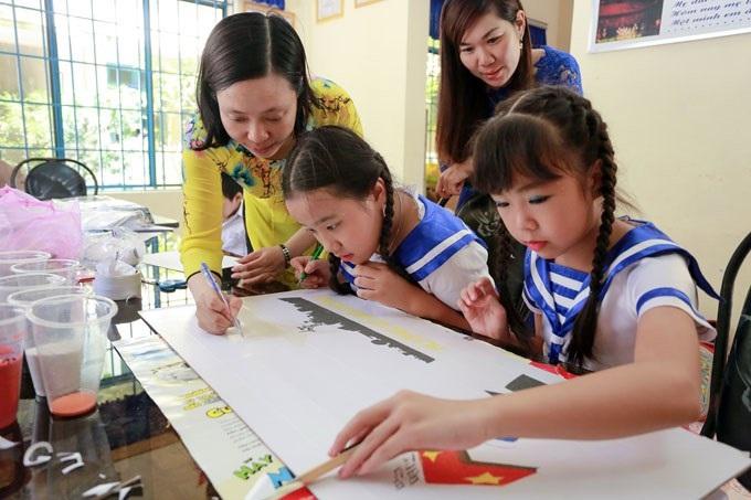 Cô giáo đang giảng bài cho học sinh tiểu học.