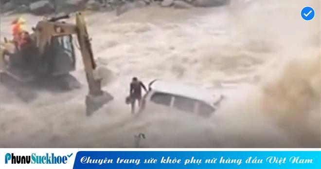 Tài xế ô tô rơi vào tình cảnh 'ngàn cân treo sợi tóc' khi bị dòng lũ dữ cuốn trôi, may mắn được 'vị cứu tinh' máy xúc đến giải vây kịp thời