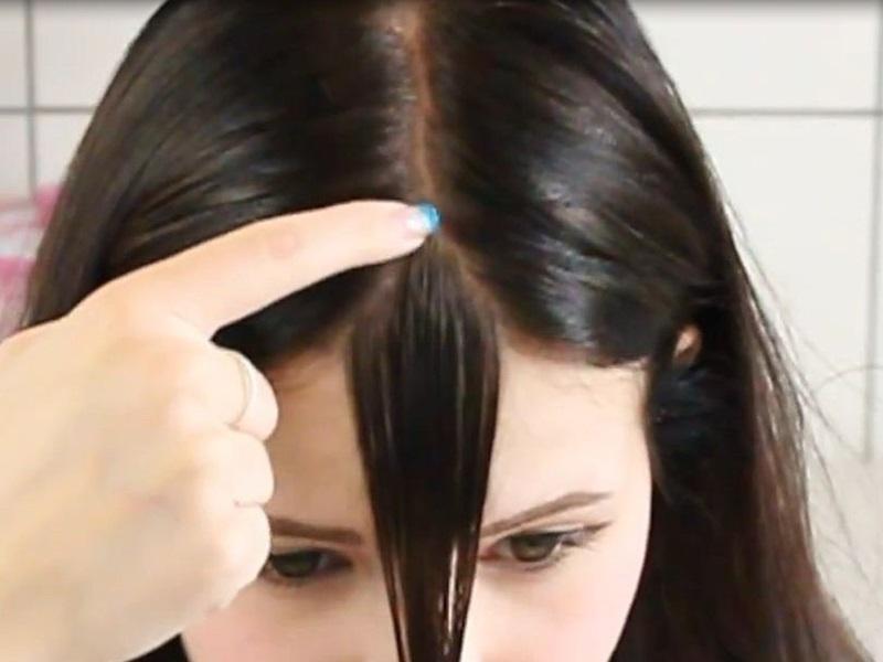 Bạn rẽ lấy 1 lọn tóc ở chính giữa đầu sao cho chân tóc tạo hình mũi tên đối xứng.