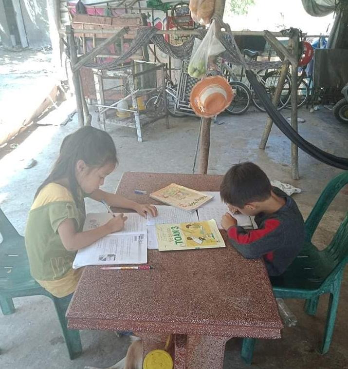 Hai đứa em Hiền chăm chỉ học bài ngoài sân
