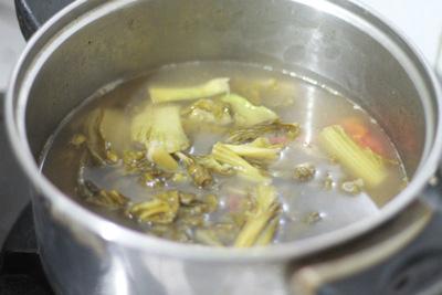 Sau khi xào dưa cải chua, thêm nước, cà chua và nấm hương, nấu sôi